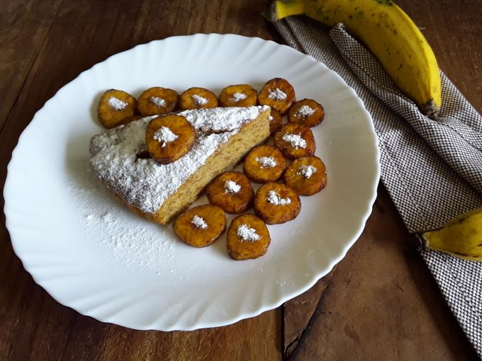 Eggless Banana Cake, garnished with powdered sugar and deep-fried ripe nendran banana chips.