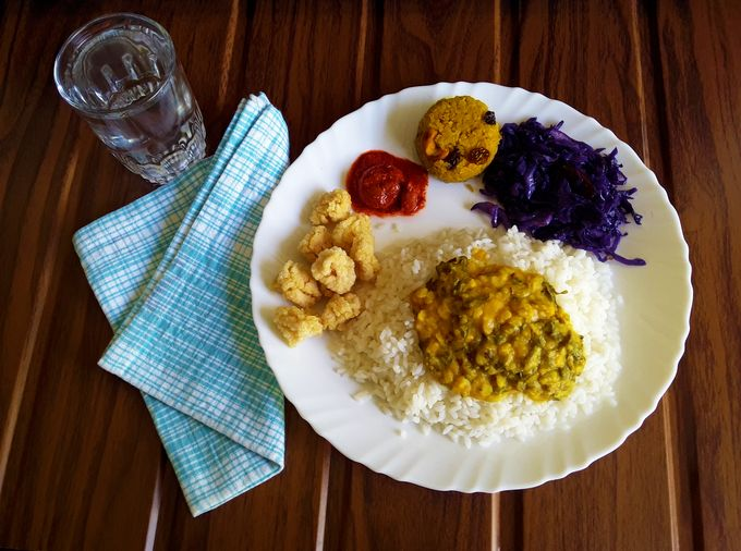 Rice with collard dal, deep-fried odis, tender mango pickle, red cabbage stir-fry and sweet khichadi.