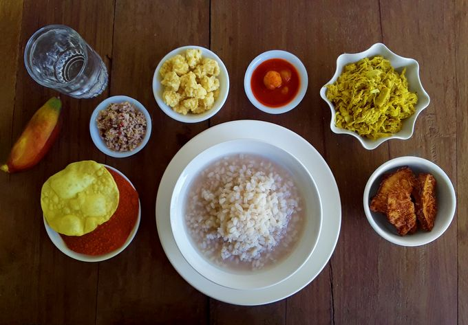 Paej (unpolished par-boiled rice gruel) with ambya phulla chutney (mango blossom chutney) accompanied by kadgi chakko (tender jackfruit side dish), ponsa kadgi podi (deep-fried tender jackfruit chips), papodu (papads), mirsange appolu (chili papads) and odis (deep-fried, sun-dried spicy rice balls), and a lick of acerola cherry pickle.