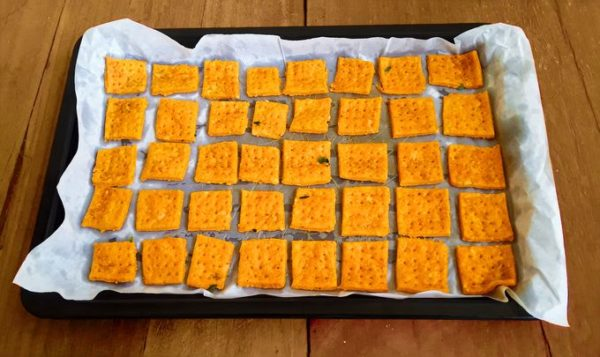 Hot and spicy, quick and easy, cheesy, savory, light and crispy, crunchy, yummy cheddar cheese biscuits on a baking tray.