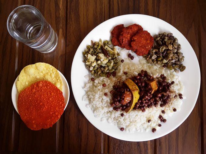 Tori Bendi on a pile of rice with clove beans-potato stir-fry, kirla bhojjo, cow pea stir-fry, pappad and happolu